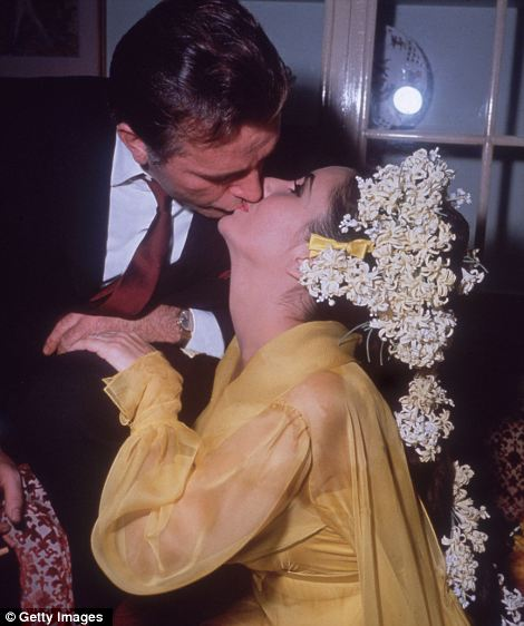 Flowers in her hair Elizabeth Taylor sits on a sofa kissing Richard Burton, her fifth husband on their first wedding day