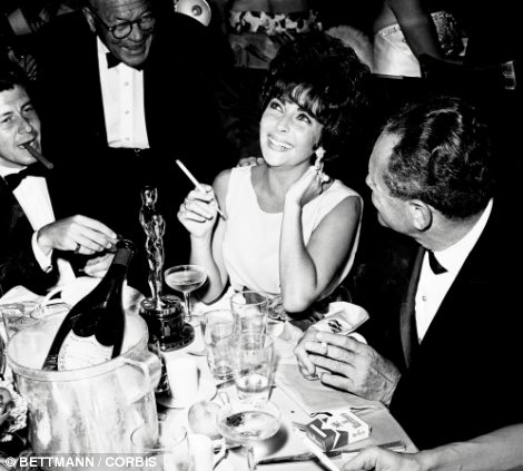 Party girl: Taylor and fashion designer Halston celebrating her 64th birthday at the legendary Studio 54 nightclub in New York (left) and celebrating her Oscar win in 1961