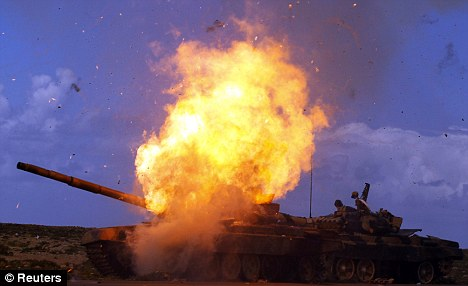War?: A tank belonging to forces loyal to Gaddafi explodes after an air strike by coalition forces, along a road between Benghazi and Ajdabiyah
