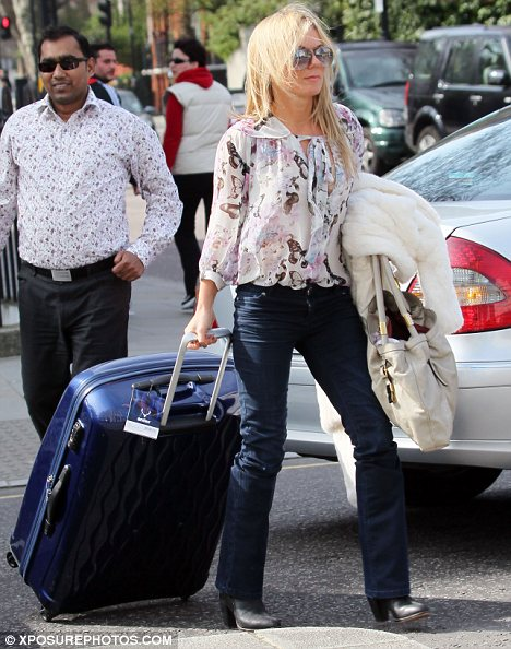 Traveling light? Geri Halliwell arrived at her boyfriend's home with a huge blue suitcase which she struggled to carry earlier today