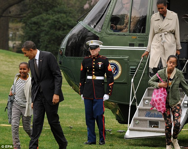 Great to be home: President Obama chats with daughter Malia as the First Family steps off Marine One on the South Lawn of the White House on Wednesday