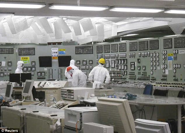 People work in the control room of reactor No. 2 with restored lighting at the earthquake and tsunami affected Fukushima Daiichi nuclear power plant
