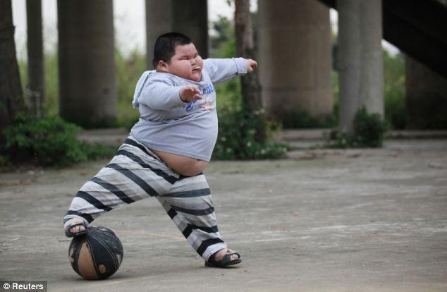 Having a ball: Hao stretches to reach a basketball while sucking on a lollipop near his home