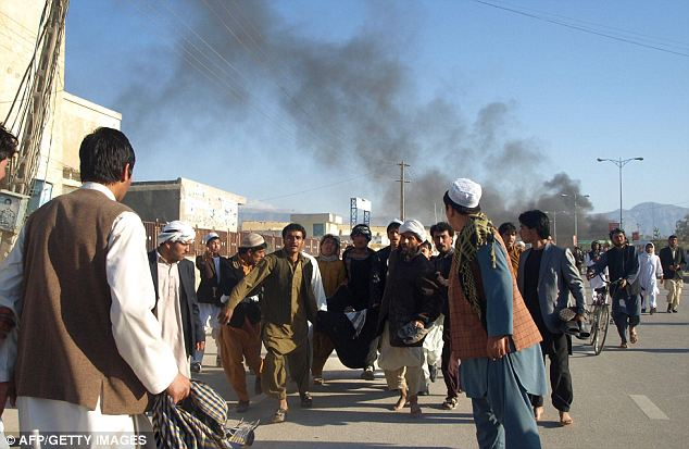 Wounded: Afghans carry a man wounded by security guards when protesters attacked the UN headquarters in Mazar-i-Sharif