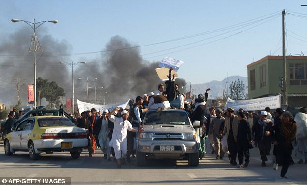 Attack: Smoke billows from the UN headquarters after protesters attacked the compound in Mazar-i-Sharif