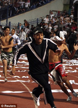 Zamalek fans run towards the pitch