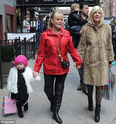 Three's company: Tori Spelling held hands with her mother Candy Spelling and daughter Stella McDermott while walking in New York yesterday