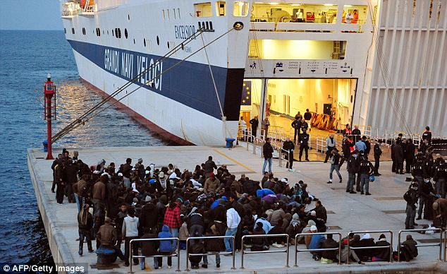 Transfer: North Africans wait to be transferred on to a cruise ship for transport to the mainland for processing