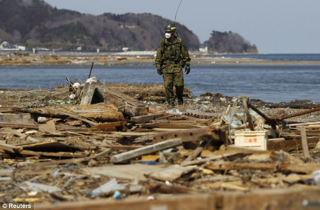 A member of the Japan Self Defense Force searches for victims along the Japanese coastline, almost a month after the tsunami hit