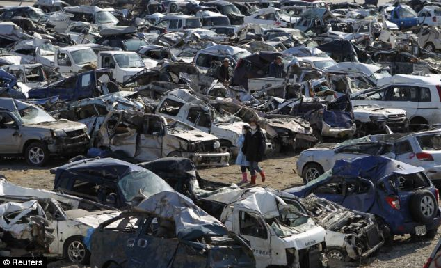 qDestruction: Two young Japanese women look for their cars among hundreds of damaged vehicles