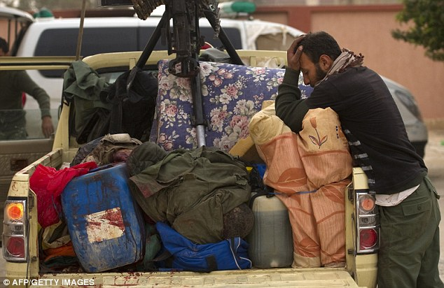 Worn down: A Libyan rebel fighter mourns over a fallen comrade whose body lies in the back of their vehicle