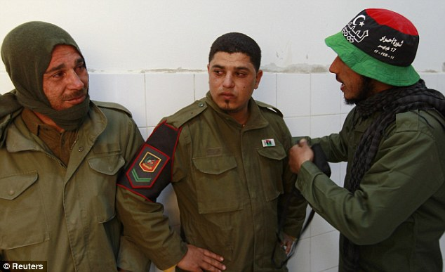 Shocked: Rebel fighters comfort one another at Ajdabiya