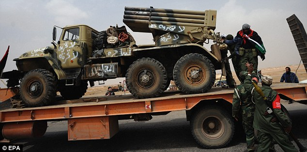 On the move: Libyan rebel fighters load a missile launcher on a truck from the front line on the west gate of Ajdabiya