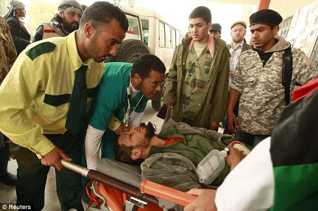 Injured: Medics wheel a rebel fighter into the hospital in Ajdabiya after the Nato attack on Brega