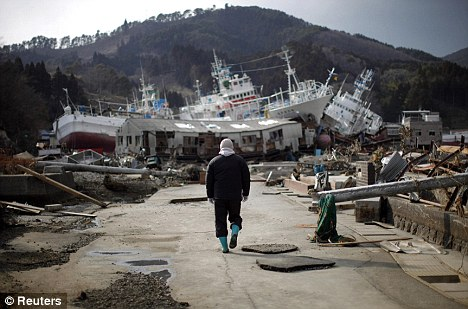 Country in turmoil: A man walks towards a boat stranded inland at Kessenuma, Japan after the earthquake and tsunami last month