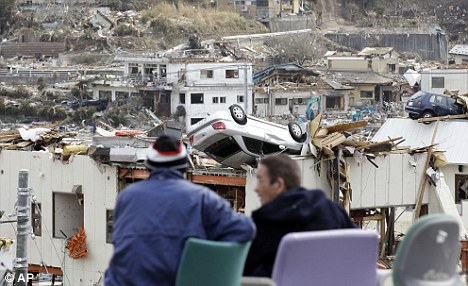 Nowhere to go: Evacuees survey their flattened town at Onagawa in north-eastern Japan