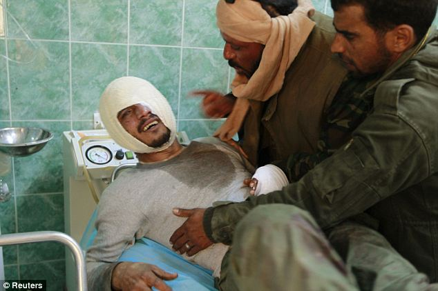 Pain: Rebel fighters comfort a wounded comrade who was brought to the hospital in Ajdabiya