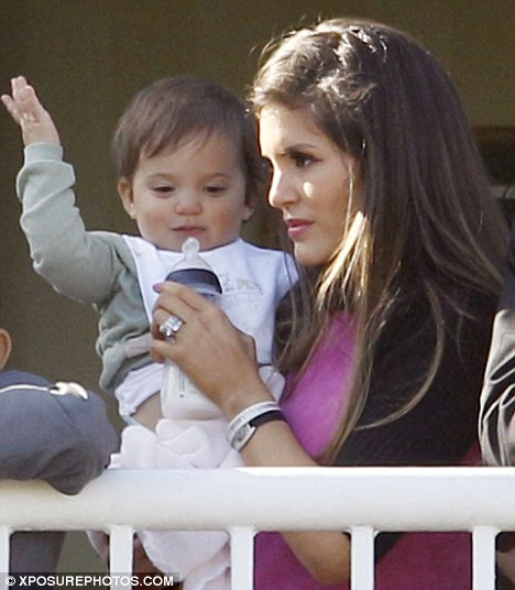 Too cute! Little Ruby Cole appeared to wave to the crowd from the VIP balcony at Aintree today as she was held by her mother Carly
