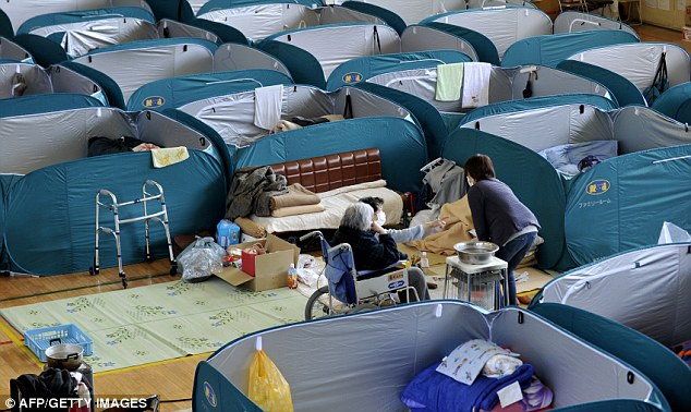 Shelter: Evacuees live in partitioned 'rooms' at a shelter for people evacuated from the Fukushima region - but they will not be allowed in until they have the 'all clear'