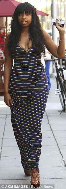 Earning her stripes: The star was make-up free and wearing a navy and yellow maxi dress with tan platform sandals