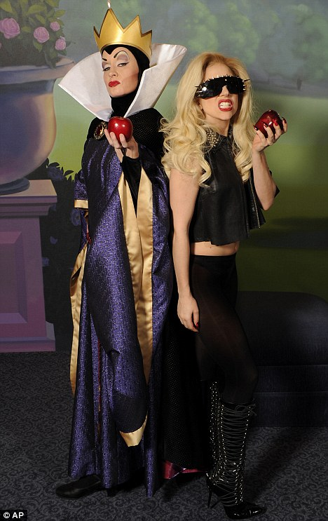 Meeting her match: Lady Gaga poses with the Evil Queen from Snow White at Disney World in Florida yesterday, both with the iconic poisoned apple in hand