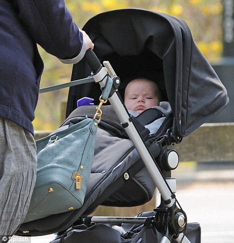 Life of privilege: The little boy surveyed the world around him as he was pushed through the park by his nanny