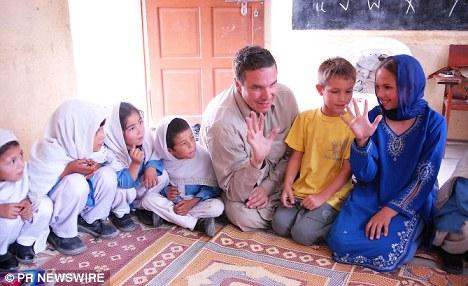 Greg Mortenson, his son Khyber, and daughter, Amira Mortenson, with students at Gultori War refugee school,