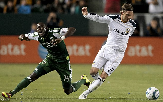Tackled: Beckham wins the ball from Portland Timbers midfielder James Marcelin during the first half of the MLS soccer match