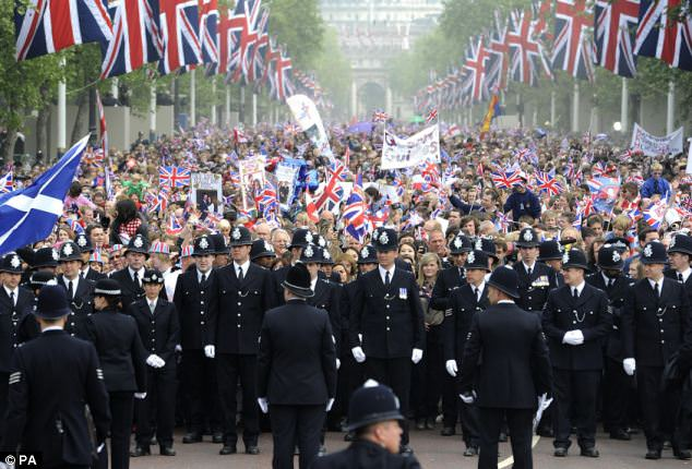 Fully staffed: Police lead the thousands of people down The Mall towards Buckingham Palace to watch Prince William and his new bride Kate on the balcony at Buckingham Palace