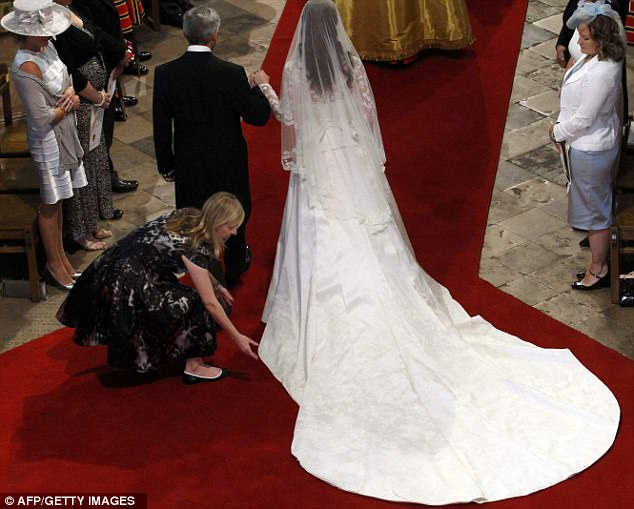 Commission of the century: Alexander McQueen's head designer Sarah Burton makes sure every detail of the dress looks perfect before the bride walks down the aisle