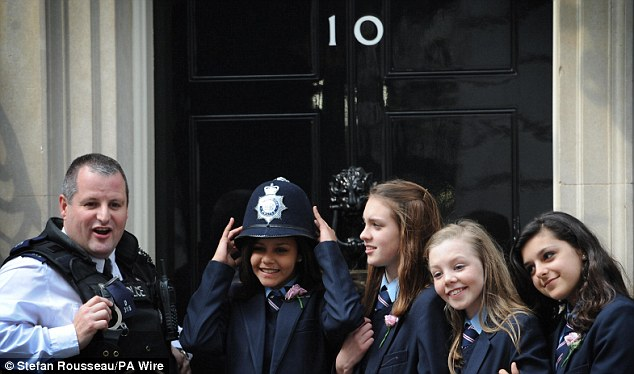 Nice hat: A schoolgirl tries on a police officer's helmet during Sam Cam's royal wedding party in Downing Street