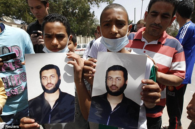 Loyal: Two boys were seen holding pictures of Gaddafi's sixth son during the guided government tour