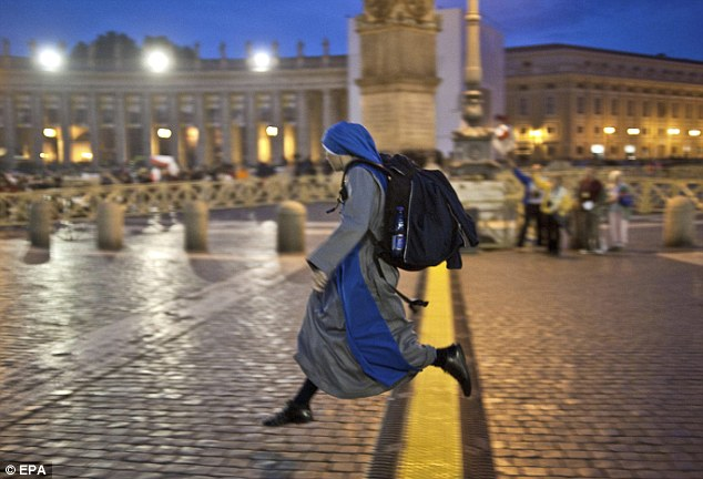 Jumping for joy: A nun leaps over a line in St Peter's Square last night. Pope John Paul will be beatified just six years after his death