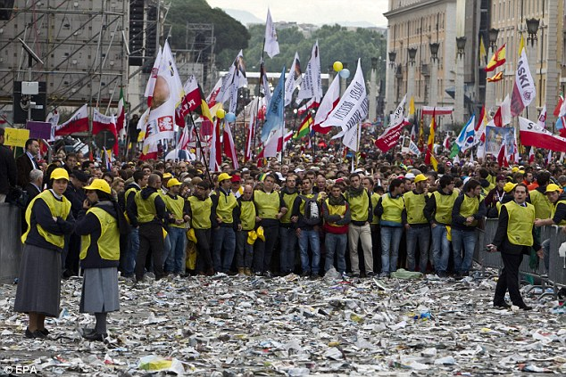 Popular: Volunteers help hold back the massive crowd in the Vatican as they throw offerings into the square