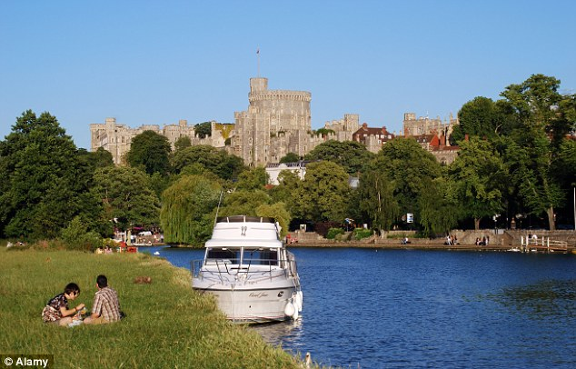 A boat is pictured on the Thames river with Windsor Castle in the background