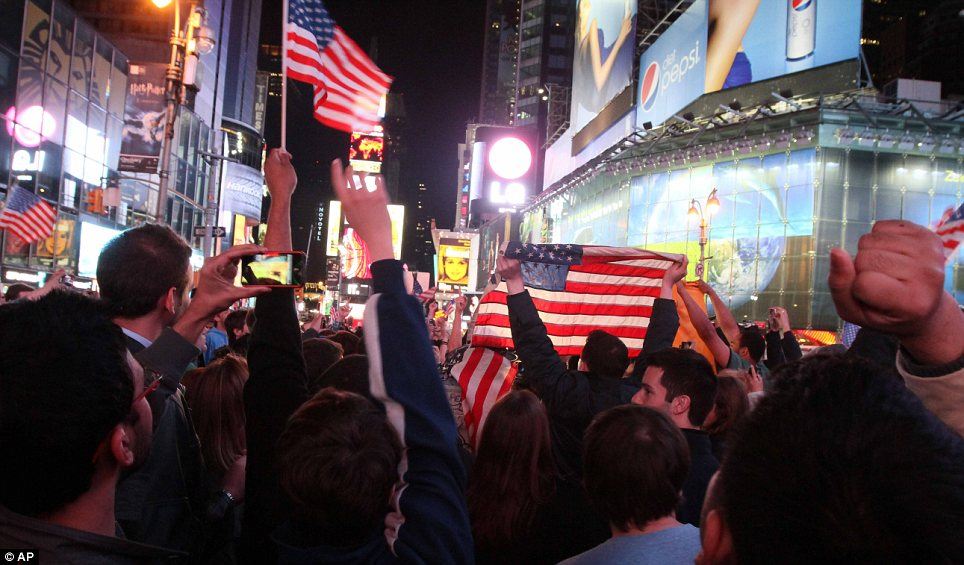 Proud to be an American: Memorable scenes emerged at Times Square in the early hours of Monday morning, with many waving U.S. flags