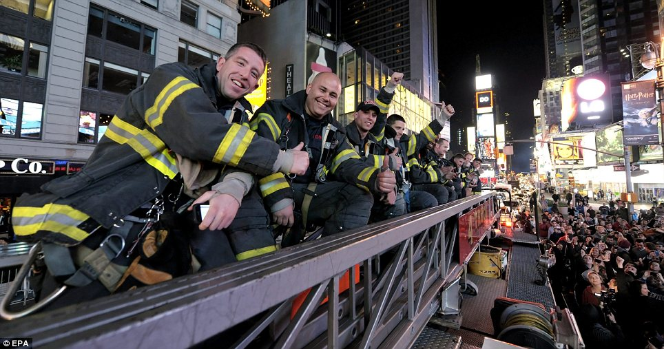 Celebration: New York City Fire-fighters join the crowd of hundreds of people in Times Square to cheer the news of the death of Osama Bin Laden