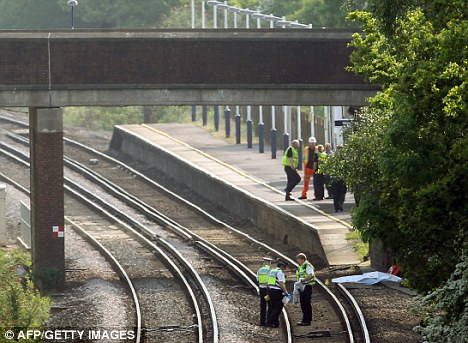 Police and forensics officers at the scene of the boy's death at Hook Railway Station, near Basingstoke, Hampshire, yesterday