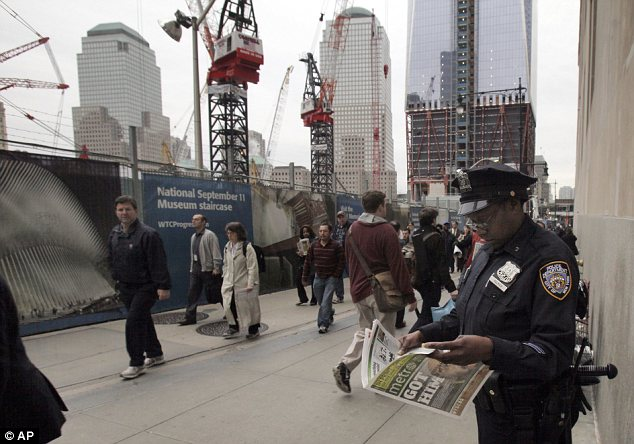 A New York City police officer reads a copy of a newspaper announcing Bin Laden's death