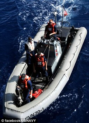 Sailors take one of the ship's smaller boats out for a test drive