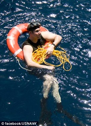 Scuba: A sailor floats in a life ring while weaning diving flippers and goggles