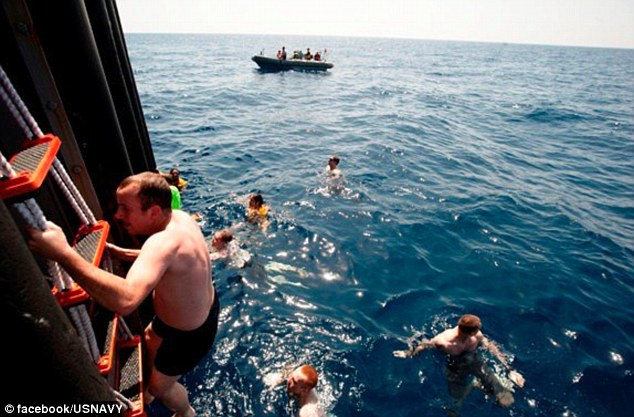 Deep blue ocean: With their shirts off and dressed only in their swimming trunks, the sailors haul themselves up a rope ladder to make another jump into the cool water