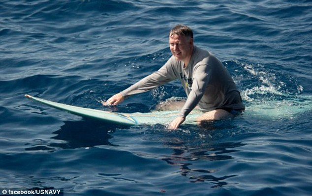 All's swell: The ship's Commanding Officer, Capt. Bruce H. Lindsey, grabs his surfboard and paddles across the sea but there's little sign of any waves
