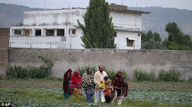 Tourist site: A Pakistani family leave after viewing the walled compound in Abbottabad where Bin Laden was caught and killed