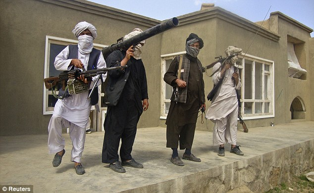 Not going to back down: Taliban fighters at an undisclosed location in Southern Afghanistan pose with weapons in a show of strength