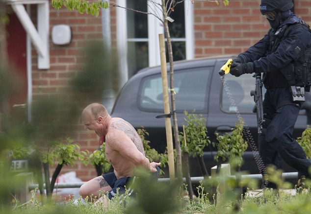Floored: Cawston falls to the floor after he is tasered outside his house in Norfolk