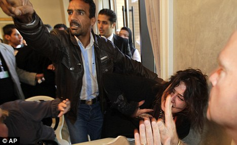Stopped: A Libyan Ministry of Information official grabs Al-Obeidi as she revealed her ordeal to western journalists at a Tripoli hotel in March
