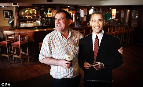 The real thing: Publican Ollie Hayes, pictured holding a cardboard cut out of Barack Obama, will not have his wares sampled when the president visits his bar
