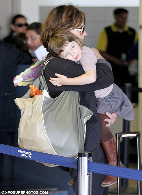 Taking a rest: The little girl appeared tired and nestled on her mother's shoulders while being carried