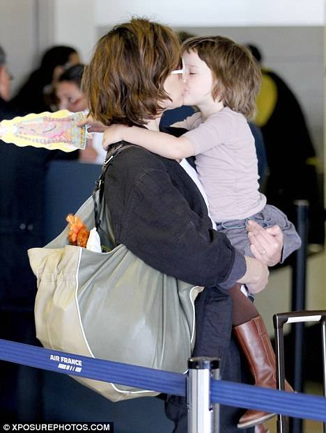 Baby love: Milla Jovovich received a big kiss from her adorable three-year-old daughter Ever Gabo while queueing up at Los Angeles airport yesterday